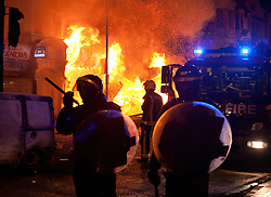 © Licensed to London News Pictures.  FILE PICTURE DATED 09/08/2011 LONDON, UK. Police officers stand in front of a blazing shop on London Road in Croydon after it was set alight by looters.  Croydon was one of several London boroughs and English cities hit by a third night of rioting and looting. Photo credit: Matt Cetti-Roberts/LNP