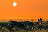 Two young local surfers in late evening catch last waves at Magic Sands Beach in Kona, HI.  Copyright 2009 Reid McNally.