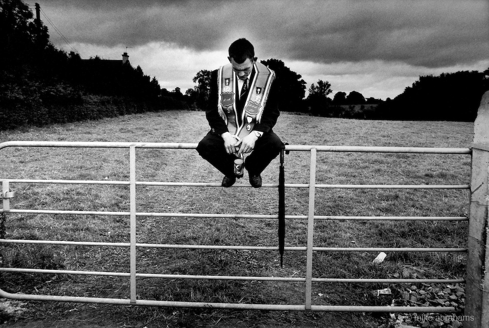A dejected Orangeman sits on a gate after having their route  from Portadown to Drumcree blocked by the RUC as a result of the march being highly provocative to the catholic residents of Garvaghy Rd. Portadown,12th July 1998. Northern Ireland