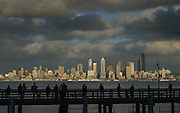 The sun breaks through the clouds and shines down on the Seattle skyline as fishermen and strollers at Seacrest Park enjoy the view. <br />