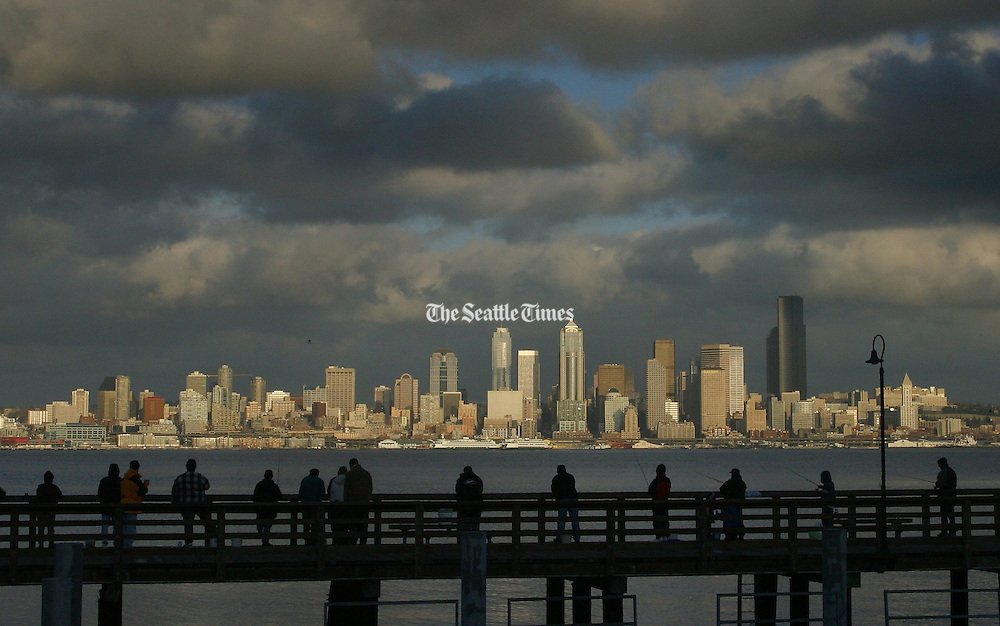 The sun breaks through the clouds and shines down on the Seattle skyline as fishermen and strollers at Seacrest Park enjoy the view. <br /> Ellen M. Banner / The Seattle Times