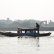 A sampan travels down the Saigon River in Ho Chi Minh City, Vietnam.