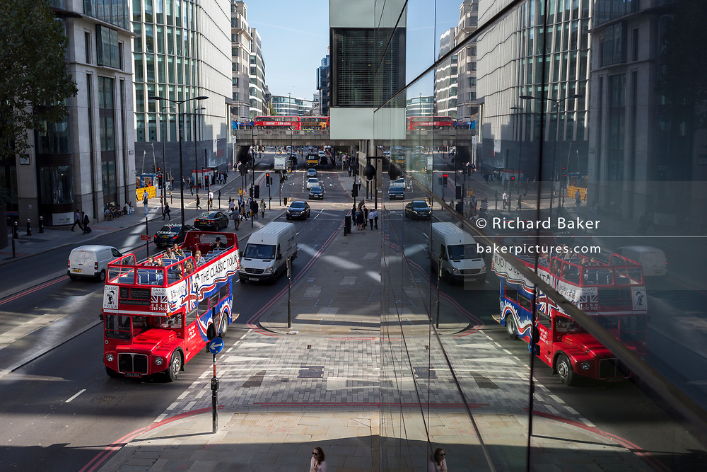 An aerial cityscape of Londoners, general traffic and an open-top double-decker tour bus on Upper Thames Street (upstream from London Bridge) in the City of London - the capital's financial district, on 11th October 2018, in London, England.