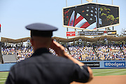 LOS ANGELES, CA - JULY 28:  A policeman salutes during the playing of the National Anthem as the American flag is shown on the stadium scoreboard before the Los Angeles Dodgers game against the Cincinnati Reds on Sunday, July 28, 2013 at Dodger Stadium in Los Angeles, California. The Dodgers won the game in a 1-0 shutout. (Photo by Paul Spinelli/MLB Photos via Getty Images)