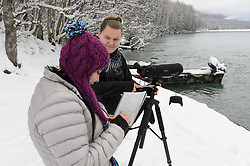 Students Heidi Kattenhorn (left) and Maggie Martin count bald eagles (Haliaeetus leucocephalus) along the Chilkat River in the Alaska Chilkat Bald Eagle Preserve, near Haines, Alaska. Since 2009, students have been conducting a weekly count of bald eagles during the fall semester for the citizen science class at the Haines School. The project is part of a field-based for-credit class, sponsored by the Takshanuk Watershed Council, in which students participate in research studies and learn about field data collection. Under the guidance of Pam Randles, Takshanuk Watershed Council Education Director, students count bald eagles in the Chilkat River Valley using spotting scopes at 10 locations and present their data at the Bald Eagle Festival held in November in Haines. During late fall, bald eagles congregate along the Chilkat River to feed on salmon. This gathering of bald eagles in the Alaska Chilkat Bald Eagle Preserve is believed to be one of the largest gatherings of bald eagles in the world.