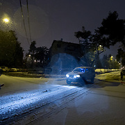 A car is seen driving as snow and rain fall in the Beit HaKerem neighborhood on January 7, 2015 in Jerusalem, Israel. (Photo by Elan Kawesch)