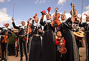 """Kiana Martinez, 14, (3rd from left), of Mariachi Aztlan de Pueblo High School, along with other members of the group, and her younger brother, Roman, 3, performs at Anita's Street Market's Miracle in the Barrio, a """"gift to the kids"""" from Grace and the late Mario Soto, owners of the market at 849 N. Anita Avenue. A few hundred children received toys, hot dogs, haircuts, and more at the 15th annual event in Tucson, Arizona, USA."""