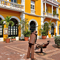 Artwork at Plaza de San Pedro Claver in Old Town, Cartagena, Colombia<br /> In a town filled with charming squares, the Plaza de San Pedro Claver stands out for its delightful artwork by Eduardo Carmona.  The wrought-iron figures depict Colombians in everyday tasks.  An example is this barber sliding his razor against a leather strop attached to his empty chair.  These whimsical statues are curtesy of the Museo de Arte Moderno.  The art museum is located nearby in a 17th century customs house.