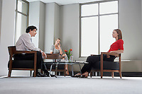 Three businesspeople sitting at table talking low angle view