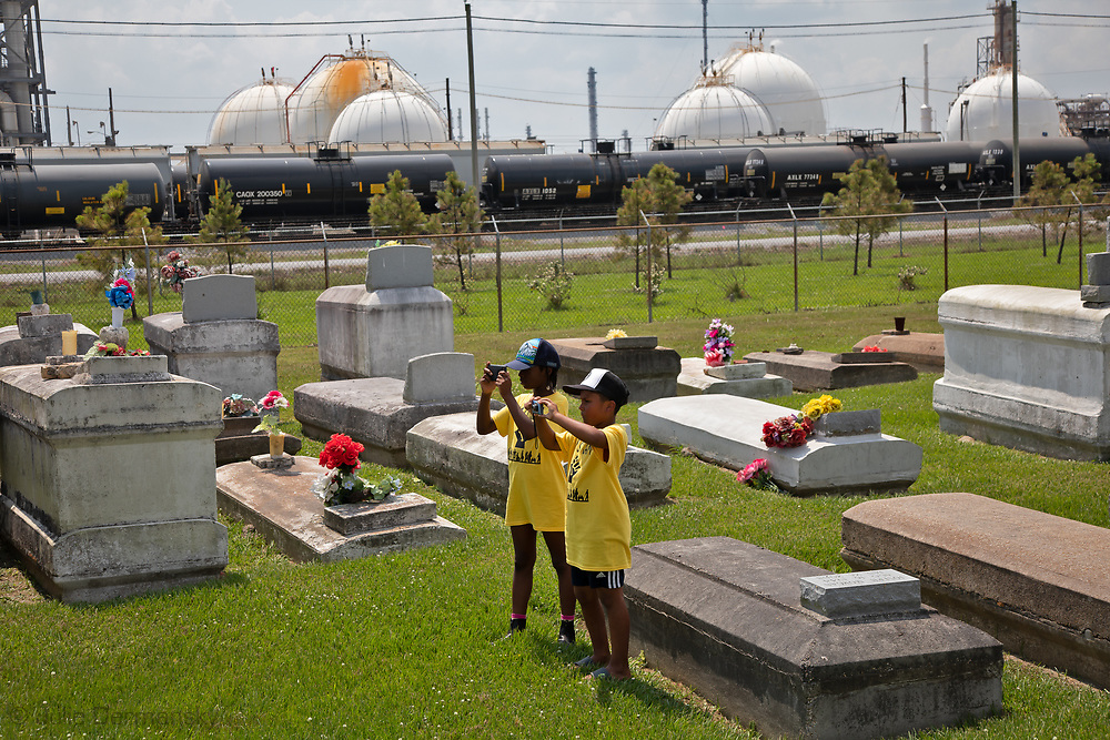 """Children with CADA and supporters at the Reveille Town Cemetery in Plaquemine, Louisiana on the fourth day of the Coalition Against Death Alley's 5 day march. The Coalition Against Death Alley (CADA), is a group of Louisiana-based residents and members of various local and state organizations, is calling for a stop to the construction of new petrochemical plants and the passing of stricter regulations on existing industry in the area that include the groups RISE St. James, Justice and Beyond, the Louisiana Bucket Brigade, 350 New Orleans, and the Concerned Citizens of St. John.  Louisiana's Cancer Alley, an 80-mile stretch along the Mississippi River, is also known as the """"Petrochemical Corridor,"""" where there are over 100 petrochemical plants and refineries. The cemetery is located within the fenceline of Westlake Chemical plant that controls acess to it."""