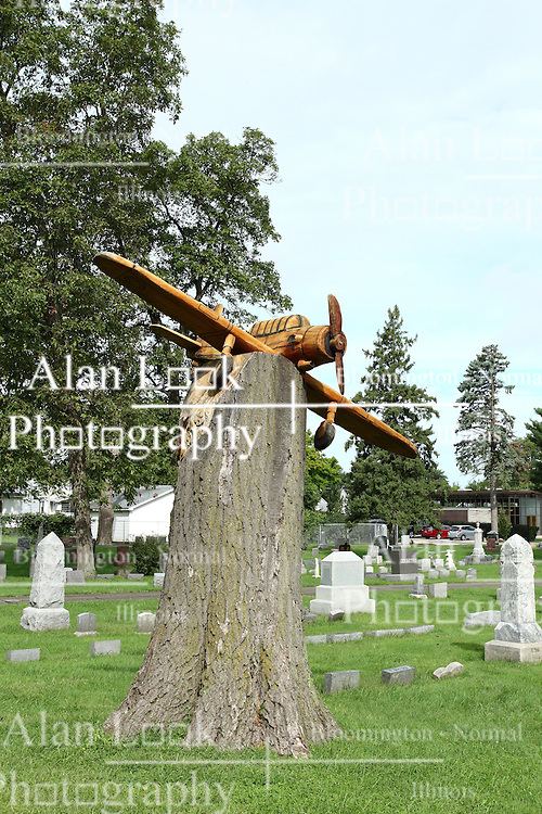 26 August 2016:  Carved Airplane Memorial in Evergreen Cemetary This sculpture by Tom Gill was carved from the tree which it now rests.  It memorializes a plane crash in 1948 in which a world war II plane was flying low and slow over the cemetery to drop poppies.  That plane crashed into a tall oak tree.  The carving was completed and erected in September of 2015.