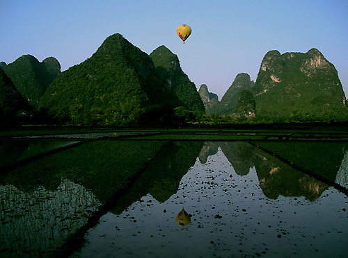 The beautiful limestone karsts in the countryside around Yangshuo are reflected in a flooded rice paddy, with a yellow hot air balloon sailing high above.
