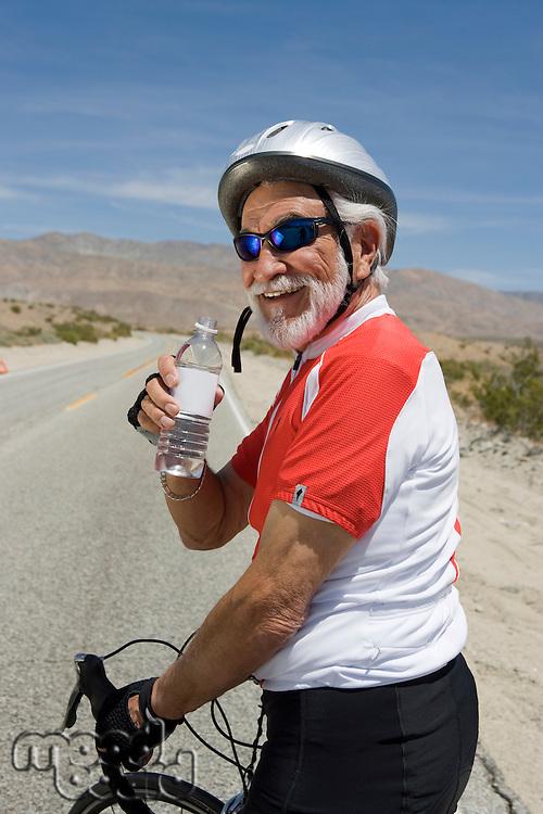 Senior man with bike drinking water