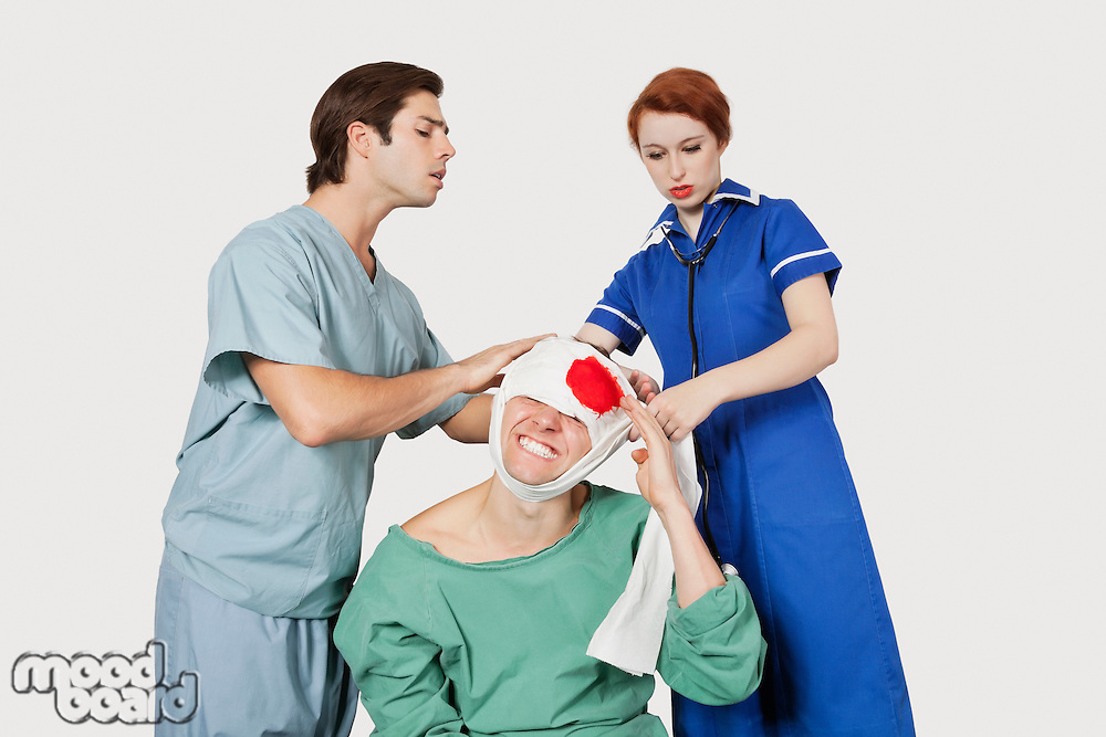 Male doctor with female nurse bandaging an injured patient against gray background