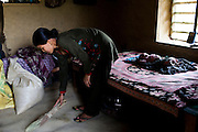 Nisha Darlami, 19, sweeps the floor as her 1 month old baby girl, Bushpa, sleeps in her mother's house in Kalyan Village, Surkhet district, Western Nepal, on 30th June 2012. Nisha eloped with her step nephew when she was 13 but the couple used contraceptives for the next 6 years to delay pregnancy until she turned 18. In Surkhet, StC partners with Safer Society, a local NGO which advocates for child rights and against child marriage. Photo by Suzanne Lee for Save The Children UK