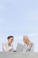 Low angle view of concentrated businesswoman using laptop while standing with coworker on terrace against sky
