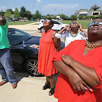Torris Purnell, from left, Contanna Purnell, Cassandra Moore and Eatrice Collins take a break from work and step outside to see the solar eclipse at Fairprk on Monday.