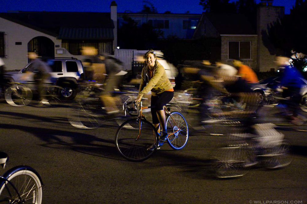 During a Critical Mass event in San Diego, Sara Hagerty stops her bike while a swarm of cyclists passes around her.