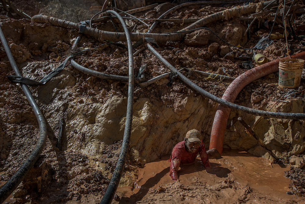 "LAS CLARITAS, VENEZUELA - JULY 20, 2016:  Thousands of Venezuelans are flocking to illegal gold mines, like this one, called ""Cuatro Muertos"" (""Four Dead"" because four miners have died here since the mine was dug) in hopes of surviving the current economic crisis by earning in gold instead of the national currency, whose value steadily falls due to the world's highest inflation.  From this remote part of the jungle the migrant miners have become the vectors of a new epidemic of malaria, because the hot, swampy conditions of the mines make for an ideal breeding ground for mosquitos. Miners spread the disease as they return home with earnings or pay visits to family members. Dozens of miners that work in this mine said that they have contracted malaria multiple times, some even dozens of times. The economic crisis has also left the government without the financial resources to control the disease - they are unable to fumigate homes, provide medicines to everyone that is sick, or even to test all patients with symptoms of malaria in many places. PHOTO: Meridith Kohut"