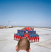 In the mid-day heat, all members of the elite 'Red Arrows', Britain's prestigious Royal Air Force aerobatic team, stand at ease and we see the back of one of the squadron's official photographers head, looking into the viewfinder of his camera to record an official photograph immediately on PDA Day at RAF Akrotiri, Cyprus. PDA (or 'Public Display Authority'), is when they are allowed by senior RAF officers to perform as a military aerobatic show in front of the public - following a special test flight when their every move and mistake is assessed and graded. Until that day arrives, their training and practicing is done in the privacy of their own airfield at RAF Scampton in Lincolnshire, UK or here in the glare of Akrotiri. The pilots are called reds and their ground crew, the Blues after their summer air show uniforms.