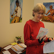 "1/24/12 -- BRUNSWICK, Maine. Brunswick's Julie Zimmerman reads a letter from an inmate participating with College Guild's curricula. Zimmerman's College Guild is a non-profit which educates and supports the sanity of inmates across the nation. From her tiny office in Brunswick, she and a part-time helper manages 50 volunteers and support 450 inmates. The part time staffer alongside Julie, who prefers to remain anonymous, noted that the waiting list nearly matches the active roster in size - without any sort of outreach. ""We get thanked so much for doing so little,"" she said. College Guild needs volunteers, Board Members and more financial support to keep up their mission. visit them online at: http://www.collegeguild.org. On the wall behind here is art done by inmates and given to College Guild in thanks for their efforts. Playboy Magazine recently recognized College Guild for their positive work with inmates.  Photo by Roger S. Duncan."