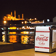 Branded Coca-Cola napkins in a dispenser on a table at a restaurant on the Galata Bridge in Istanbul, overlooking the Golden Horn and with the lights of one of the city's distinctive mosques in the background.