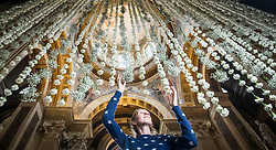 Castle Howard employee Hannah Cooke puts the finishing touches to a ÒwaterfallÓ of 3000 white carnations in the Great Hall ahead of the Castle Howard in Bloom Flower Festival in Yorkshire.
