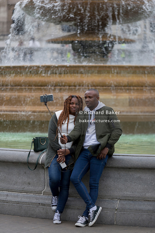 With a background of fountains, a black couple take a selfie portrait with a selfie stick, in Trafalgar Square, on 20th May 2019, in London, England.