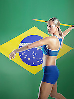 Side view of a female athlete preparing to throw javelin against white background