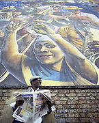 Man reading newspaper leaning against wall with mural portraying musicians.