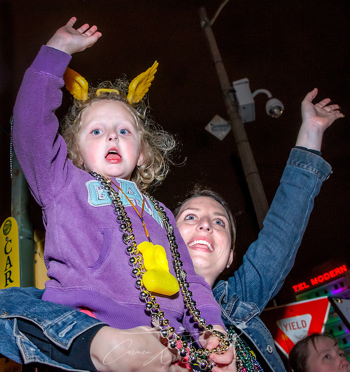 A mother and daughter wave for beads as a float rolls down St. Charles Avenue at the Krewe of Hermes Mardi Gras parade at Lee Circle, Feb. 28, 2014, in New Orleans, Louisiana. (Photo by Carmen K. Sisson/Cloudybright)