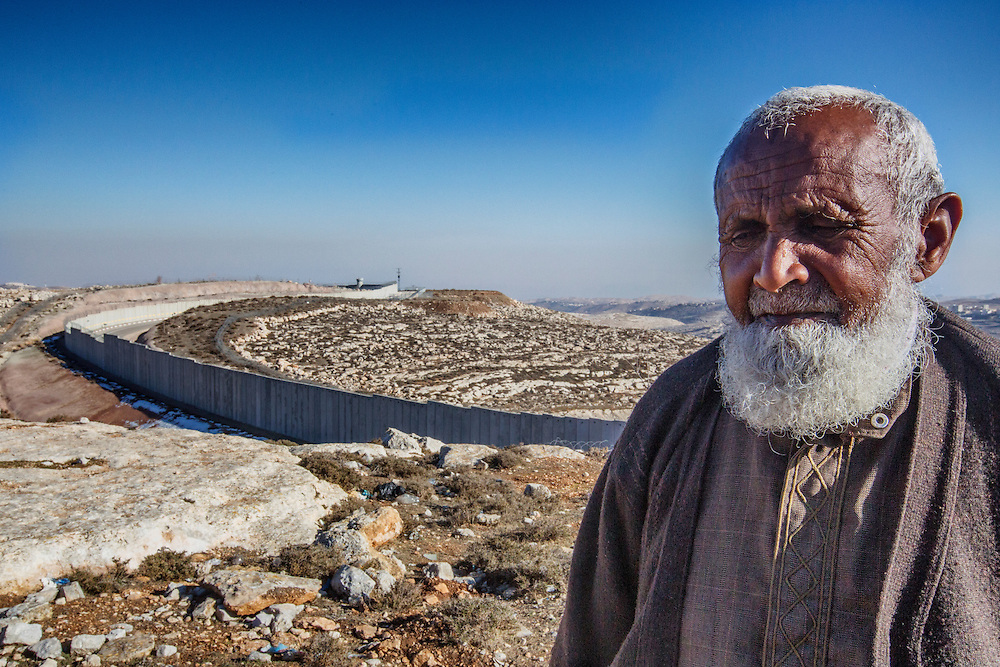 An elder of Al Ram stands in front of the Israeli-built separation wall, which has left his village only a small fraction of the grazing land it once had. Local Bedouin say the introduction of the wall has affected their lives perhaps more than anything else in the modern era. Dec. 21, 2013. West Bank, Palestinian Territories. (Photo by Gabriel Romero/Alexia Foundation ©2014)