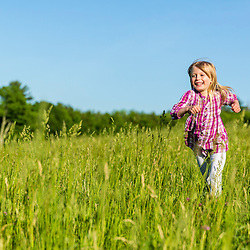 A young girl runs in a field in Epping, New Hampshire.