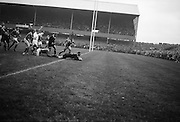 Tremain, all blacks, goes over for his sides important try, with Irelands Kiernan tackling to no avail, left,..Irish Rugby Football Union, Ireland v New Zealand, Tour Match, Landsdowne Road, Dublin, Ireland, Saturday 7th December, 1963,.7.12.1963, 12.7.1963,..Referee- H Keenen, Rugby Football Union, ..Score- Ireland 5 - 6 New Zealand, ..Irish Team, ..T J Kiernan, Wearing number 15 Irish jersey, Full Back, Cork Constitution Rugby Football Club, Cork, Ireland,..J Fortune, Wearing number 14 Irish jersey, Right Wing, Clontarf Rugby Football Club, Dublin, Ireland,..P J Casey, Wearing number 13 Irish jersey, Right Centre, University College Dublin Rugby Football Club, Dublin, Ireland, ..J C Walsh,  Wearing number 12 Irish jersey, Left Centre, University college Cork Football Club, Cork, Ireland,..A T A Duggan, Wearing number 11 Irish jersey, Left Wing, Landsdowne Rugby Football Club, Dublin, Ireland,..M A English, Wearing number 10 Irish jersey, Stand Off, Landsdowne Rugby Football Club, Dublin, Ireland, ..J C Kelly, Wearing number 9 Irish jersey, Captain of the Irish team, Scrum Half, University College Dublin Rugby Football Club, Dublin, Ireland,..P J Dwyer, Wearing number 1 Irish jersey, Forward, University College Dublin Rugby Football Club, Dublin, Ireland, ..A R Dawson, Wearing number 2 Irish jersey, Forward, Wanderers Rugby Football Club, Dublin, Ireland, ..R J McLoughlin, Wearing number 3 Irish jersey, Forward, Gosforth Rugby Football Club, Newcastle, England, ..W J McBride, Wearing number 4 Irish jersey, Forward, Ballymena Rugby Football Club, Antrim, Northern Ireland,..W A Mulcahy, Wearing number 5 Irish jersey, Forward, Bective Rangers Rugby Football Club, Dublin, Ireland,  ..E P McGuire, Wearing number 6 Irish jersey, Forward, University college Galway Football Club, Galway, Ireland,  ..P J A O' Sullivan, Wearing  Number 8 Irish jersey, Forward, Galwegians Rugby Football Club, Galway, Ireland,..N A Murphy, Wearing number 7 Irish jersey, Forward, Cork Constitut