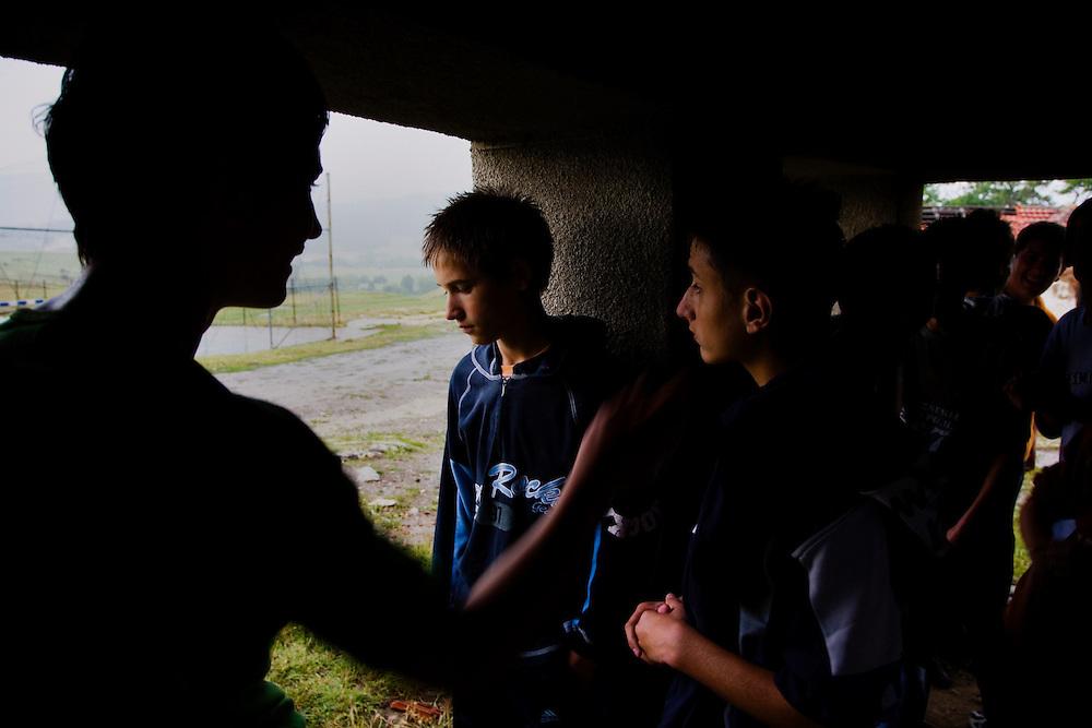 Albanian boys take shelter from a sudden rainstorm at a school above Shtime, Kosovo.