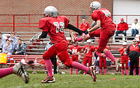 """Jordan McCrea flanked by Brian McCullough take to the field at kickoff wearing """"pink socks"""" in dedication and to raise funds and awareness for Breast Cancer Research Saturday morning.   (Karen Bobotas/for the Laconia Daily Sun)"""