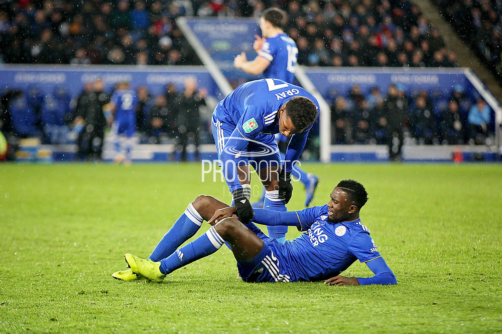 CAPTION CORRECTION Leicester City midfielder Demarai Gray (7) tends to an injured Leicester City midfielder Onyinye Wilfred Ndidi (25) during the quarter final of the EFL Cup match between Leicester City and Manchester City at the King Power Stadium, Leicester, England on 18 December 2018.