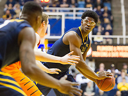West Virginia Mountaineers forward Devin Williams (5) looks to pass to West Virginia Mountaineers forward Jonathan Holton (1) against the Oklahoma State Cowboys during the second half at the WVU Coliseum.
