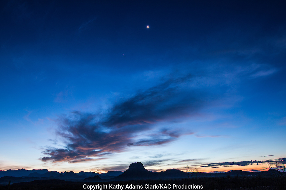 Crescent moon and Jupiter with silhouette of mountains at sunrise in Big Bend National Park, Texas.