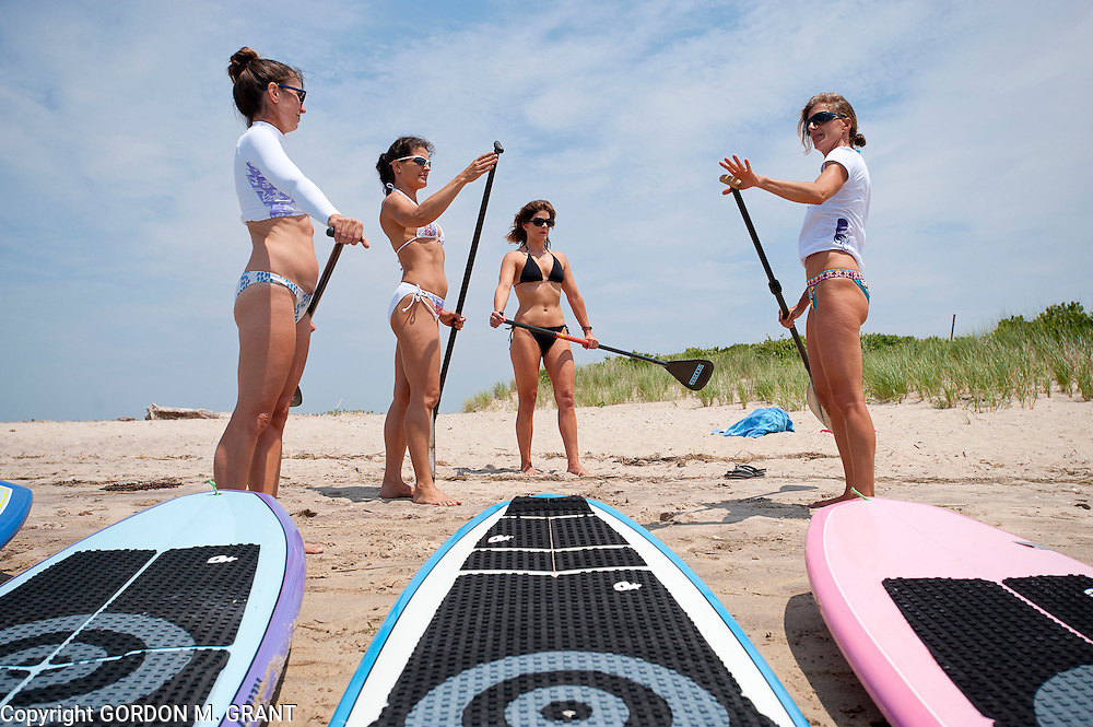 Gina Bradley, the owner of Paddle Diva, right, a paddleboard instructor, gives a lesson to (l-r) Peri Allen, Jennifer Ford, and Meg Salen, at Louse Point in East Hampton.  (June 24, 2010)