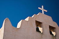 An historic adobe church sits under blue skies in New Mexico.