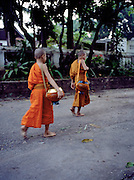 Novice monks with bowls of food from morning offerings.