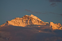 Berner Oberland, Switzerland. A close-up of the Jungfrau at sunset.  The clouds take on a pink/grey hue.