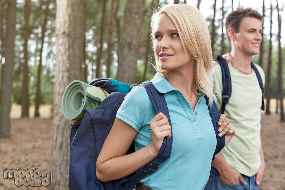 Beautiful young woman with man trekking in forest