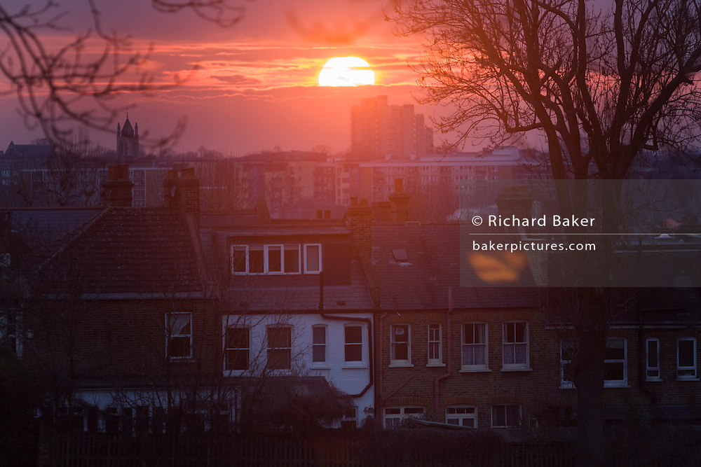 Lens flare from setting sun between layers of cloud over inner-city south London rooftops.