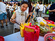 09 NOVEMBER 2017 - BANGKOK, THAILAND:  A woman lights incense before praying at the Erawan Shrine on the 61st anniversary of the shrine's dedication. The Erawan Shrine is one of the most popular shrines in Bangkok. It was dedicated on November 9, 1956, after a series of construction accidents at what was then the Erawan Hotel (since torn down and replaced by the Grand Hyatt Erawan Hotel). The statue in the shrine is Phra Phrom, the Thai representation of the Hindu god of creation Brahma. It is a Hindu shrine popular with Thai and Chinese Buddhists because it is thought that making an offering to the Phra Phrom will bring good fortune.   PHOTO BY JACK KURTZ