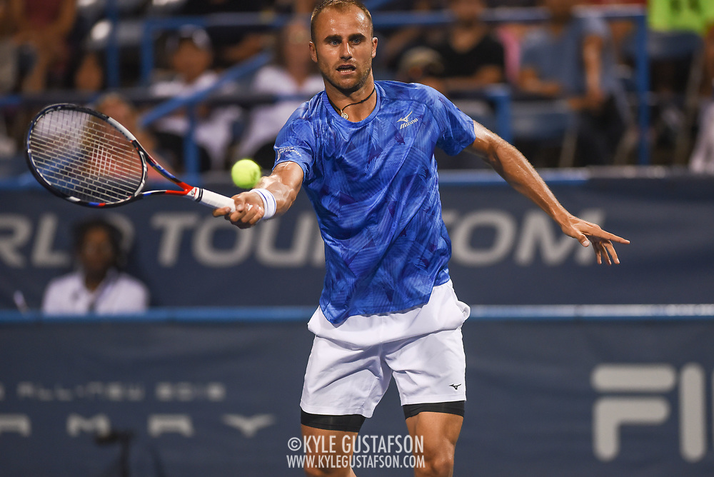 MARIUS COPIL stretches for a forehand during his second round match at the Citi Open at the Rock Creek Park Tennis Center in Washington, D.C.