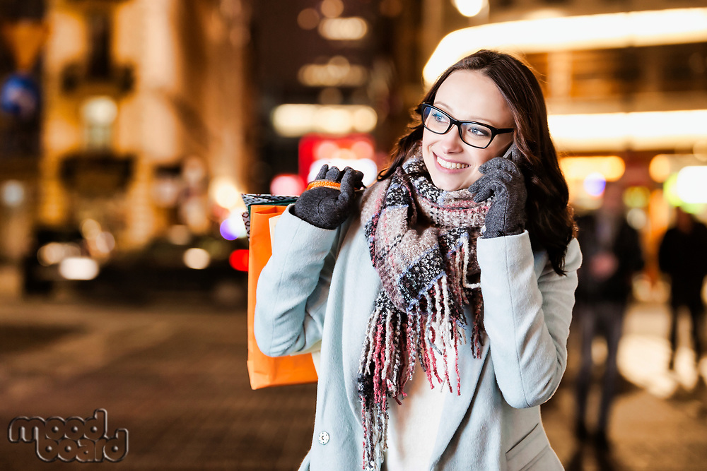 Portrait of young attractive woman smiling and talking on smartphone while holding paper bags at night shopping