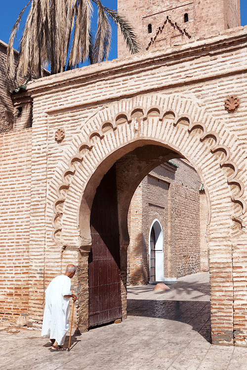 Old man walks in front of the Koutoubia mosque in Marrakech.