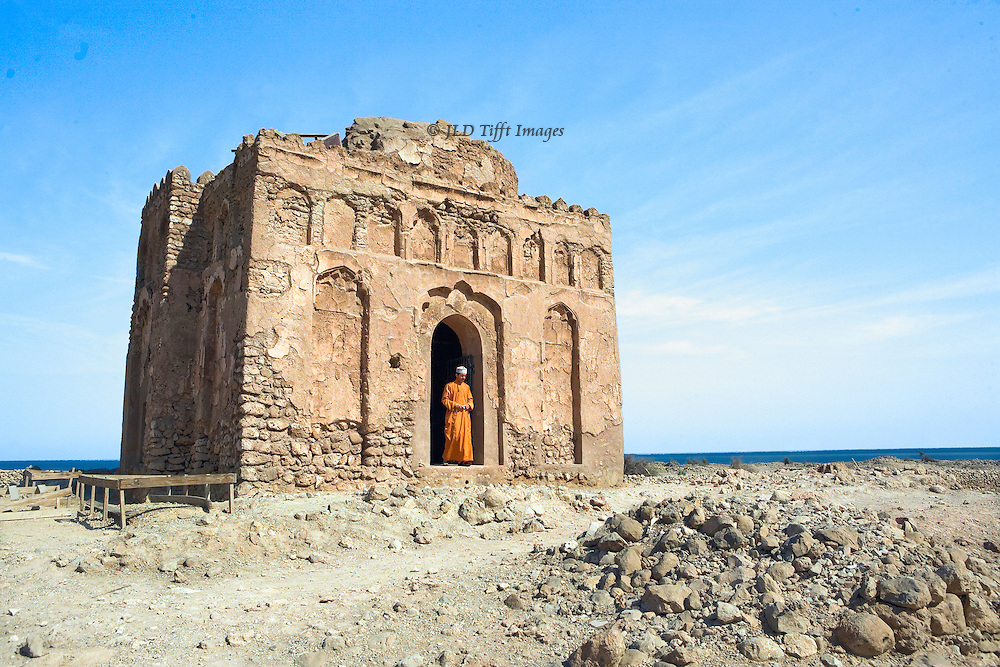 Oman, ruins of the city of Qalhat.  Only the mosque of Bibi Maryam remains, built in the 13th century when Qalhat was a wealthy trading port, visited by Marco Polo, Ibn Battuta.  Earthquake levelled it in 14th century.  Single figure of a man in the doorway and outside the small, symmetrical structure.